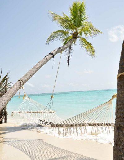 A hammock near the clear blue water